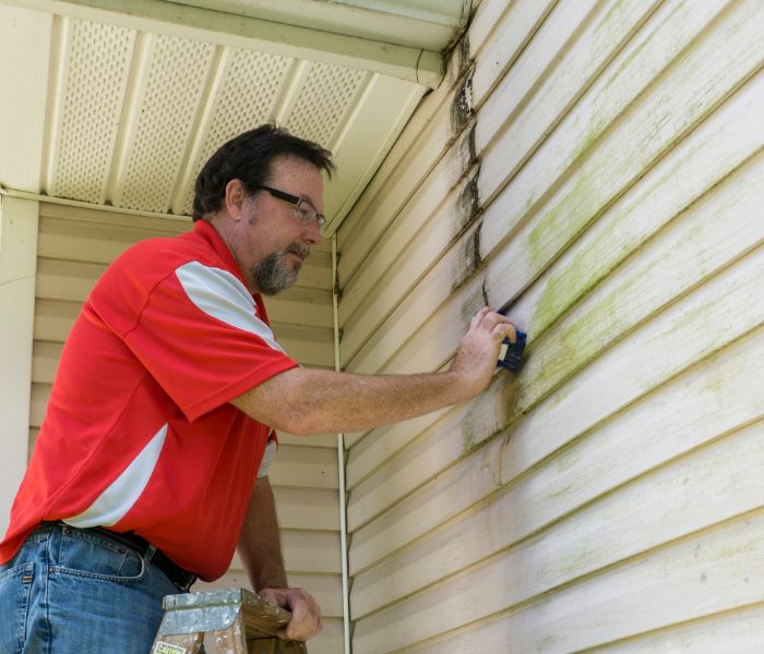 technician doing exterior house cleaning West Bloomfield